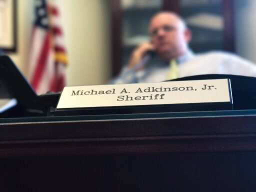Sheriff Adkinson sitting behind desk with his nameplate in the foreground