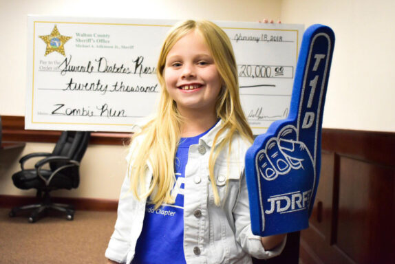young girl with giant blue foam finger standing in front of a large check for twenty thousand dollars