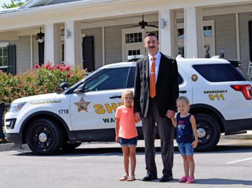 investigator holding the hands of 2 little girls standing in front of a walton county sheriff vehicle