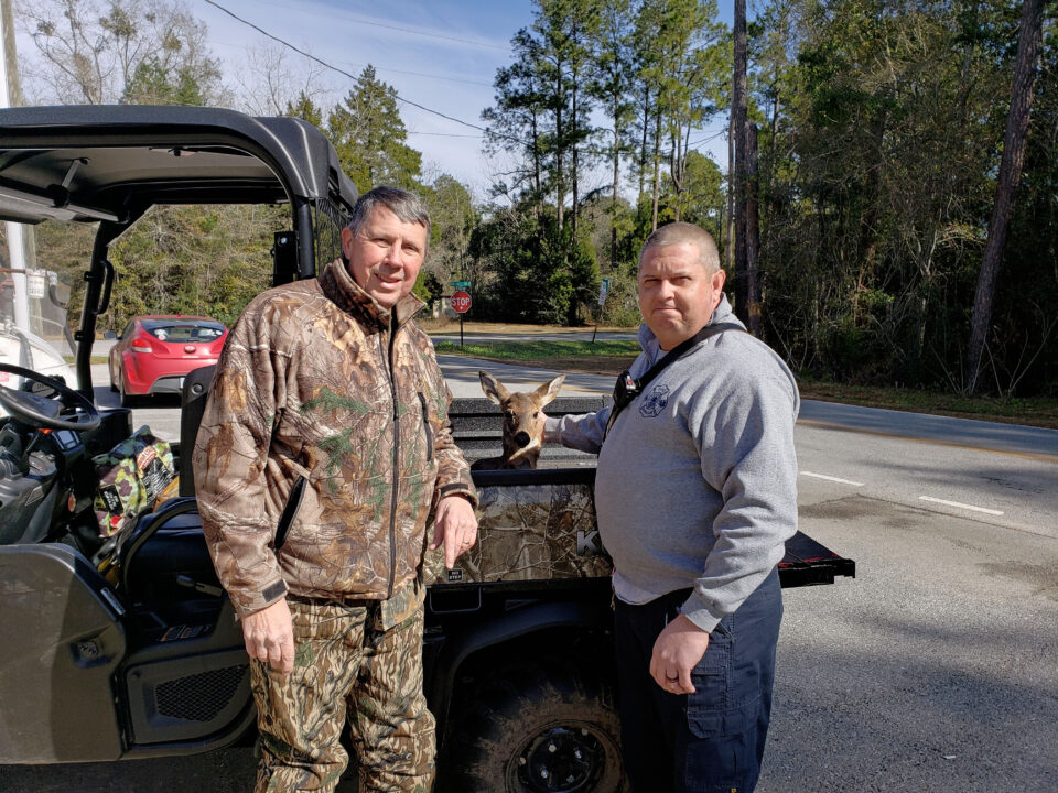 Man in camouflage jacket and camouflage pants and a firefighter in navy pants and a grey pullover standing in front of a camouflage utility vehicle with a young deer inside