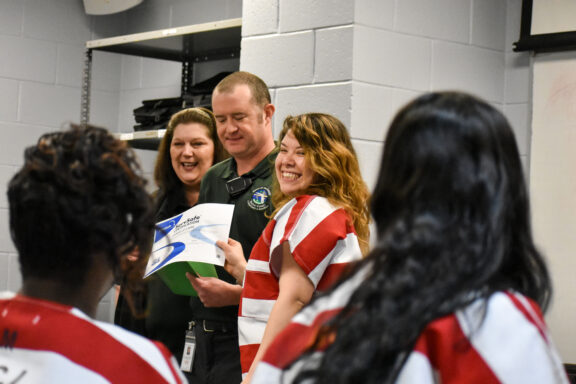 A felame inmate smiles when receiving her ServSafe certificate during her incarceration at the Walton County Jail.