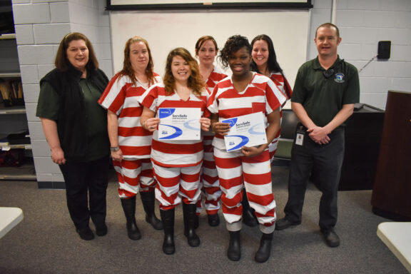 The inmates, which include three women from Escambia County, pose with their certificates.
