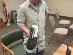 Suspect, Seth Snowden, holding his tennis shoes that he used to kick multiple vehicles over several days.