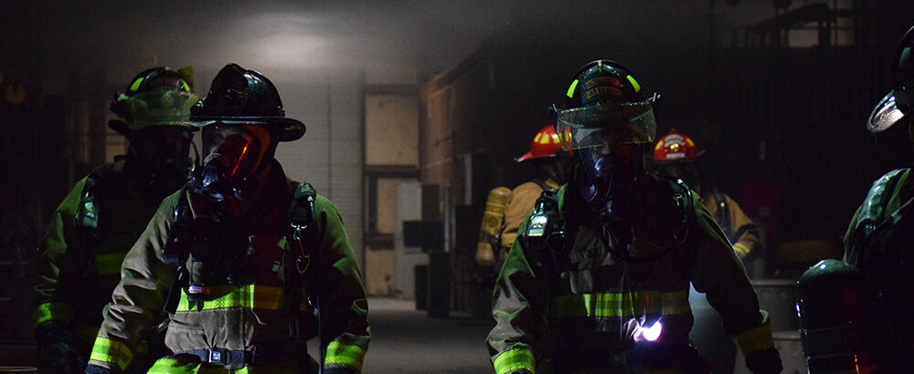 Firefighters walking through dark, smoky building