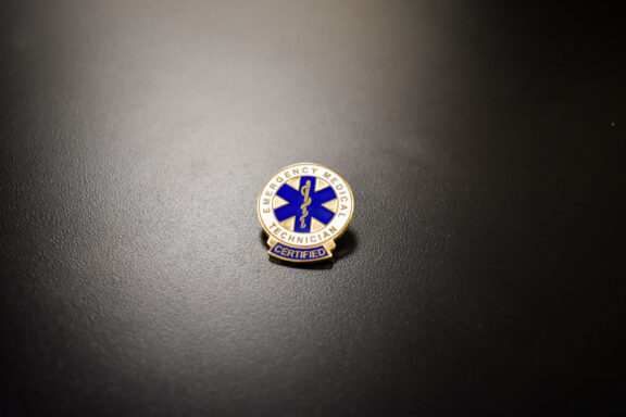An EMT pin sits on a table at the EMT Graduation Ceremony.