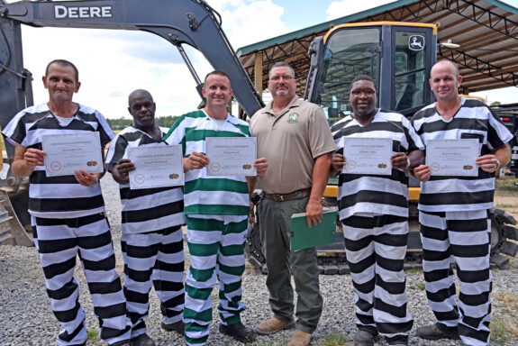 Walton County Jail Inmates Holding Up Certificates of Completion for Heavy Equipment Program