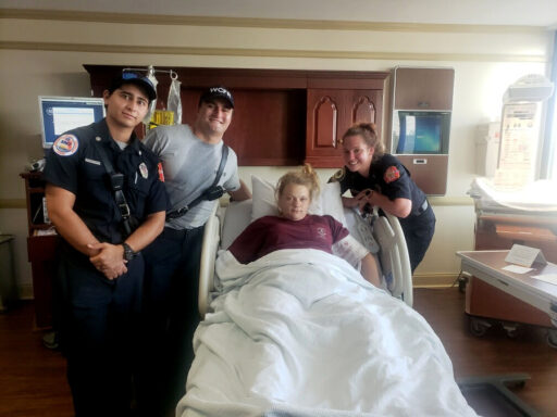 EMTs and Paramedics standing around hospital bed with mother who just had twins