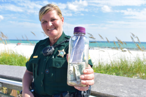 Sergeant Paula Pendleton holds a bottle that washed up on a Walton County beach.