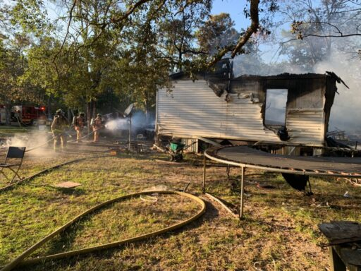 Burned Mobile Home Next to Trampoline