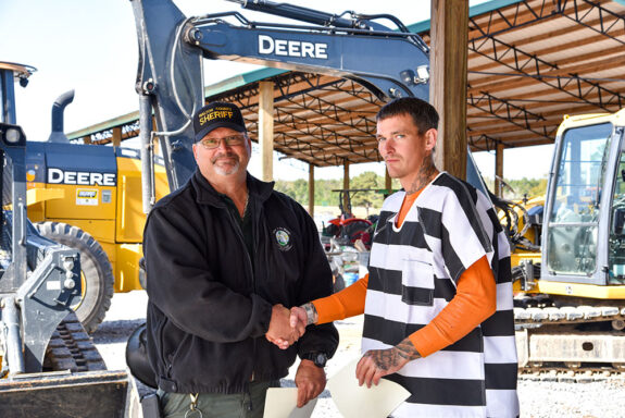 Inmate shaking instructor's hand at Heavy Equipment Graduation Ceremony
