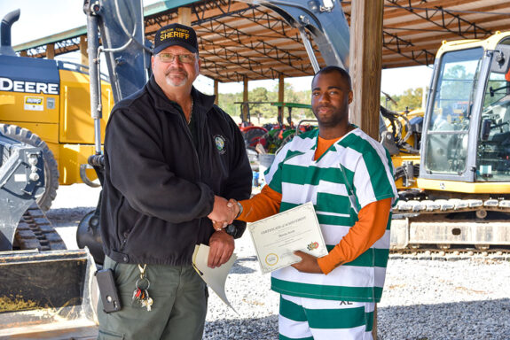 Inmate shaking his instructor's hand holding his certificate at the Walton County Jail Heavy Equipment Graduation Ceremony