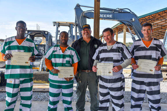 Four inmates holding up their heavy equipment certificates at walton county jail graduation ceremony