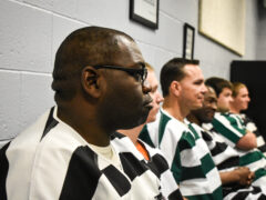 Inmates seated during graduation ceremony.