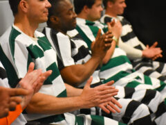 Inmates clapping during graduation ceremony.