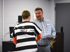 John Greehalgh, Northwest Florida State College welding instructor, shakes the hand of an inmate receiving his certificate.