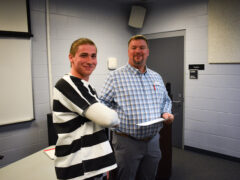 John Greehalgh, Northwest Florida State College welding instructor, smiles with an inmate receiving his certificate.
