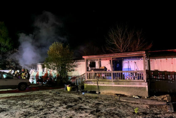 Mobile Home with Smoke Coming From the Left Side of the Home