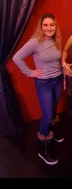 Photo of white female in blue jeans, boots and a long sleeve pink shirt.