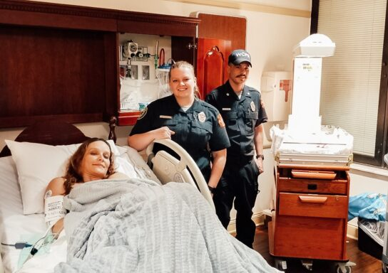 Mother in hospital bed with a paramedic and EMT smiling standing next to her
