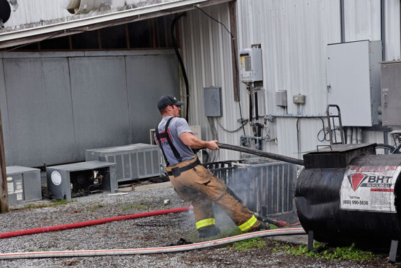 Firefighter with bunker pants on pulling a hose