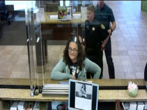 Woman standing in line at a bank with a deputy standing behind her.