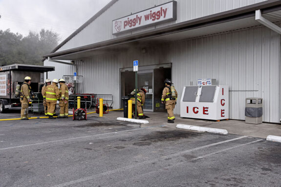 Firefighters working out front of a Piggly Wiggly with smoke coming out