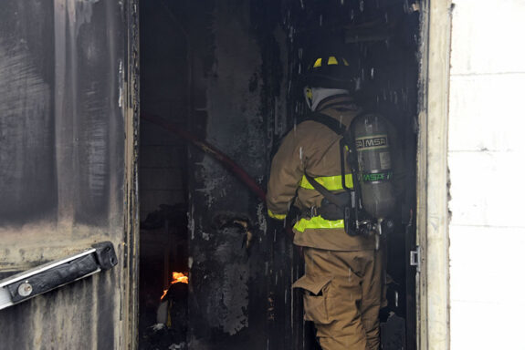 Firefighter inside dark, smoky room putting out fire