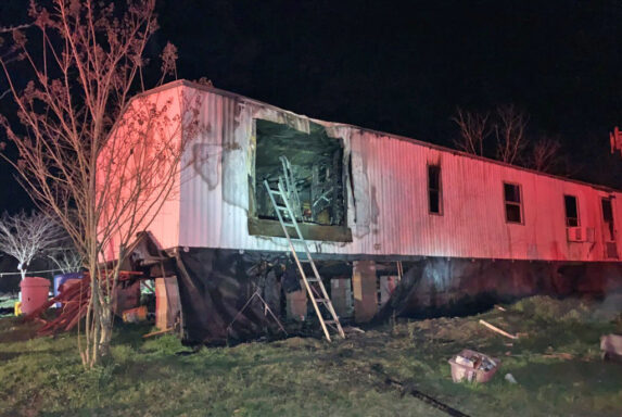 Ladder leaning up against single wide mobile home with smoke damage