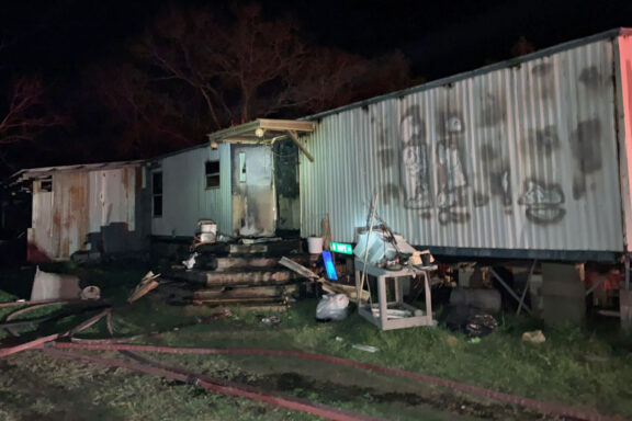 Front of single wide mobile home with damage from structure fire