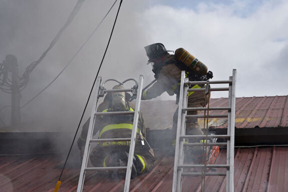 Firefighters using chainsaw on metal roof