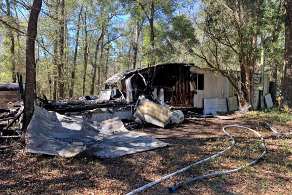 Hole in the side of mobile home after structure fire
