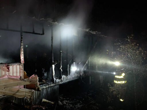 Firefighter shining a flashlight into a damaged mobile home at night following a structure fire