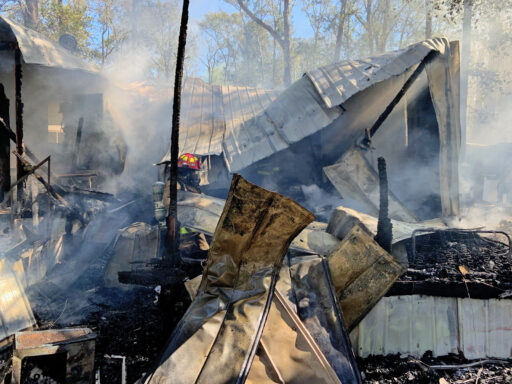 Firefighter walking through rubble following a mobile home fire