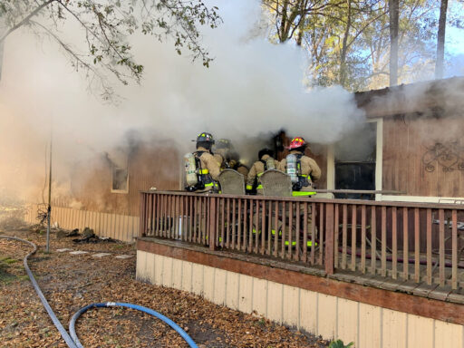 Firefighters entering the front door a mobile home with smoke coming out of it.