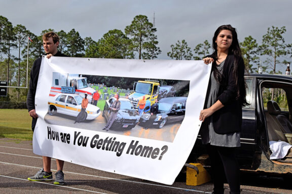 "Male and female teenager holding a banner that reads ""how are you getting home?"""
