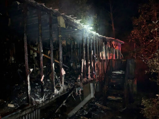 Charred Mobile Home at Night Following a Structure Fire