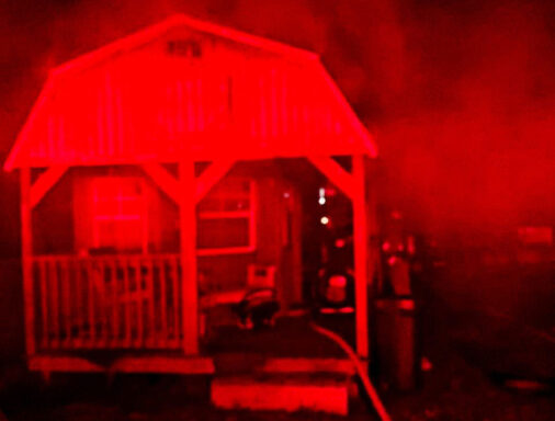 Small residential home with smoke coming from the home in the middle of the night