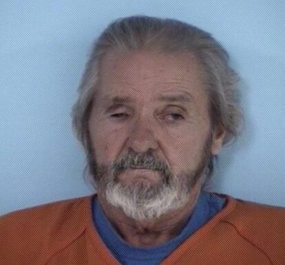 Mug shot of a white male with a beard and gray hair.