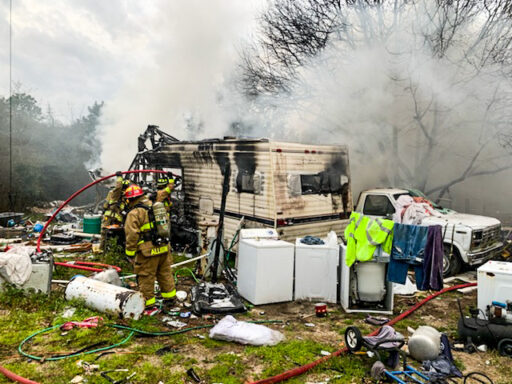 Firefighter working a fire that broke out in a fifth wheel camper