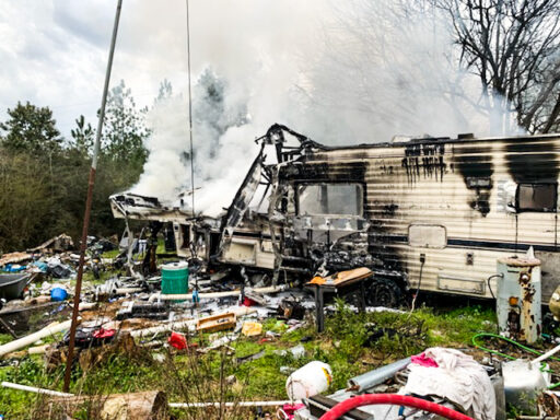 Fifth wheel camper with smoke coming out of it surrounded by debris