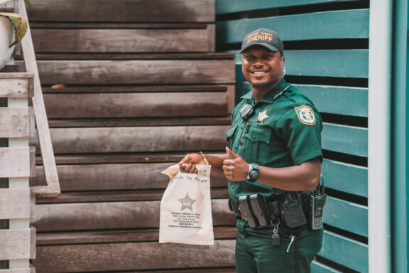 Deputy holding plastic bag holding a thumbs up.