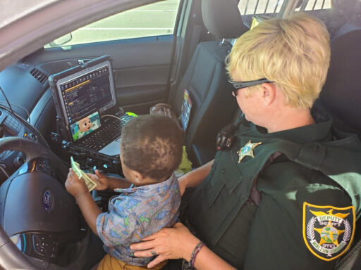 A female deputy with a child on her lap in a patrol car watching cartoons.