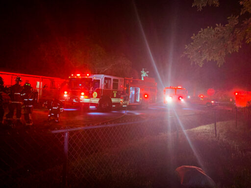 Fire Engines with bright red and white lights in the street near a home at a structure fire
