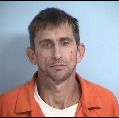 Mug shot of a white male with brown hair and short stubby facial hair.
