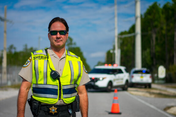 A white male with sunglasses on stands in the roadway wearing a safety vest.,