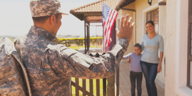Military member waving at family on a porch.