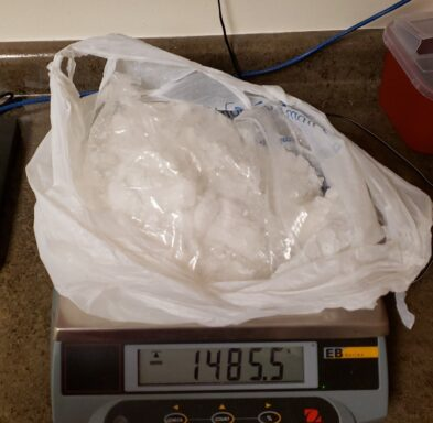 a white plastic bag full of a white powdery substance on a scale than reads more than 1400 grams.