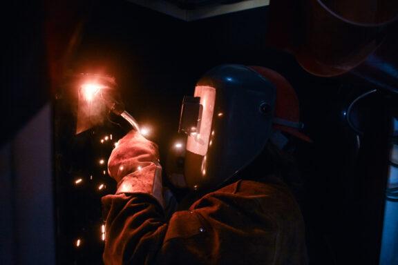 A woman wearing a welding helmet sparks her torch as she welds.