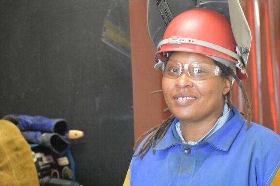 A woman smiles wearing a welding helmet.