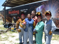 Four woman in welding gear pose with their instructor.